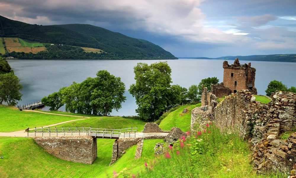 View of Loch Ness with grass and a small bridge in the foreground